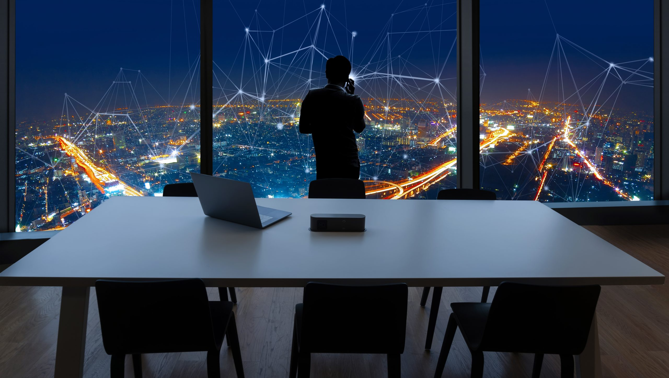 Businessman standing using smart phone and Business Wireless network in office desk and windows and Bangkok city view.